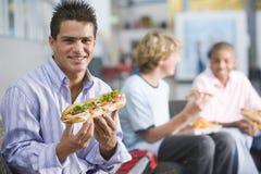 les garçons appréciant les aliments de préparation rapide déjeune d'adolescent ensemble Photo libre de droits