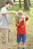 les garçons attrapent outre d'afficher leurs deux jeunes photographie stock