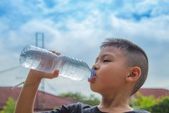 Les garçons boivent l'eau froide photo stock
