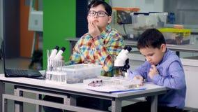 Les garçons dans le laboratoire réalisant l'étude, expérience de la science 4K banque de vidéos