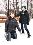 Les garçons de la préadolescence en parc de ville de neige ont l'amusement Images libres de droits