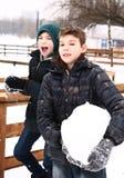 Les garçons de la préadolescence en parc de ville de neige ont l'amusement Photographie stock
