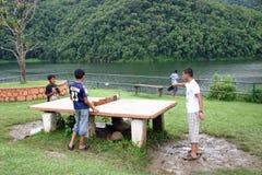 Les garçons de village jouent au ping-pong par le lac Phewa, Pokhara, Népal Photographie stock libre de droits