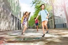 Les garçons et les filles jouent le jeu de marelle dans la cour d'école Photo stock