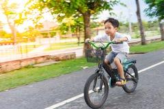 Les garçons font un cycle dans le détail de tache floue de parc de santé Photo stock