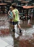 Les garçons jouant sous la pluie à côté des tables vides pendant la pluie fulminent dans St Louise à la ferme grande image libre de droits