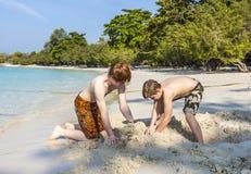 Les garçons jouent à la plage avec le sable et les chiffres de construction Image stock