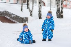 Les garçons jumeaux marchant en parc en hiver, apprennent à prendre les premières étapes Image stock