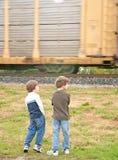 Les garçons observant un train passent Image stock