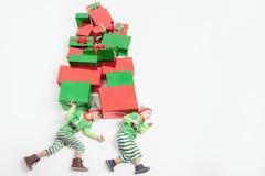 Les garçons ont habillé des costumes d'Elf tenant beaucoup de boîte-cadeau Vendredi noir Photos stock