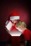 les garçons ouvrent le boîte-cadeau de Noël Photographie stock