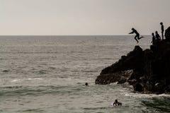 Les garçons sautant à l'eau à Ribeira de Ilhas Beach dans Ericeira Images libres de droits