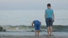 Les garçons sautent près de la mer banque de vidéos