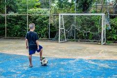 Les garçons sont sur le point de tirer le football sur le lancement photo libre de droits