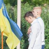Les gar?ons ukrainiens affrontent le drapeau avec remettent le coeur images stock