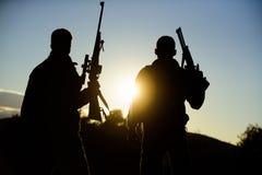 Les garde-chasse d'amis de chasseurs avec des armes à feu silhouettent le fond de ciel Environnement de nature de fusils de chass photographie stock libre de droits