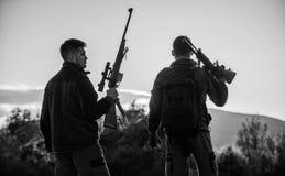 Les garde-chasse d'amis de chasseurs avec des armes ? feu silhouettent le fond de ciel Environnement de nature de fusils de chass image libre de droits