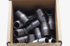 Les garnitures de pipe noires ont enfermé dans une boîte photo stock