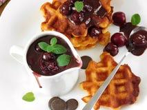 Les gaufres avec la cerise et la crème au chocolat ont servi d'un plat blanc Photo stock