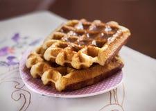 Les gaufres belges ont complété avec le caramel dans un plat photos libres de droits