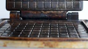 Les gaufres passionnées de cuisson de fer de gaufre sur un fond blanc banque de vidéos