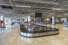 Les gens à la ceinture de bagages à l'intérieur du nouveau terminal à l'aéroport de mars Image libre de droits
