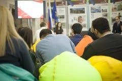 Les gens à la présentation s'asseyent dans les chaises molles Tabourets capitonnés gonflables Meubles multicolores salle photographie stock libre de droits