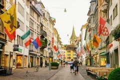 Les gens à la rue piétonnière de Rennweg avec des drapeaux à Zurich Photo stock