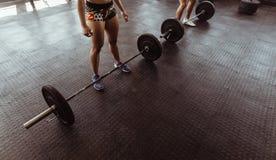 Les gens à la séance d'entraînement de gymnase avec les poids lourds Photo libre de droits