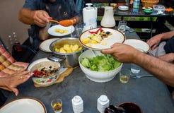 Les gens à la table complètement de la nourriture Image stock