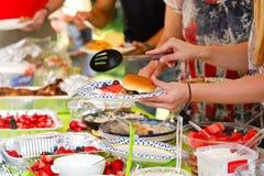 Les gens à un pique-nique de Potluck d'été photos stock