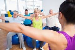 Les gens établissant avec des haltères dans le centre de fitness Image libre de droits