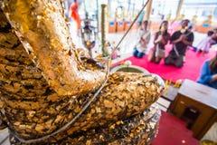 Les gens adorent la couverture de statue de Bouddha avec la feuille d'or dans le temple de la Thaïlande photo stock