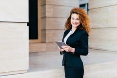 Les gens, les affaires, les innovations et le concept de technologie La belle femme bouclée heureuse avec le rouge a peint des lè image stock