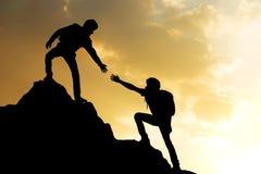 Les gens aidant sur s'élever maximal de fond de montagne et de lever de soleil Images libres de droits