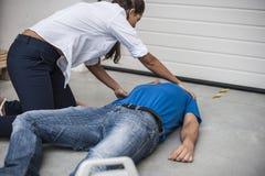 Les gens aidant un homme inconscient photographie stock