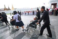 Les gens aident l'aîné sur le fauteuil roulant aux dévotions pour l'enterrement du roi Photographie stock libre de droits