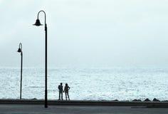 Les gens aiment les lumières de mer de côte abandonnées par main de promenade la soirée Images stock