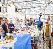 Les gens alignés aux poissons contre Photo stock