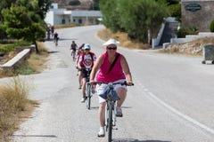Les gens allant en vélo dans la ville dans les Milos, Grèce Beaucoup de tou Photographie stock libre de droits