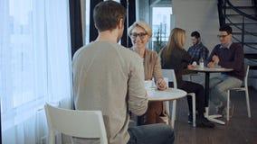 Les gens appréciant le café, travaillant et communiquant en café pendant le matin Photos stock