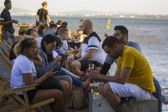 Les gens appréciant une boisson près de la rivière photo stock