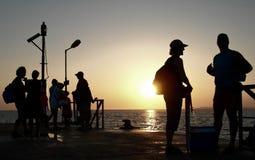 Les gens attendant au coucher du soleil patiemment photo libre de droits