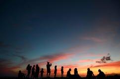 Les gens au coucher du soleil par la plage Photographie stock