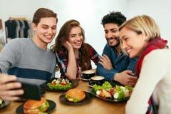 Les gens au dîner prenant des photos au téléphone Vidéo d'amis appelle photos stock