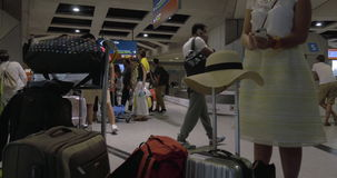 Les gens au secteur de retrait des bagages de l'aéroport banque de vidéos