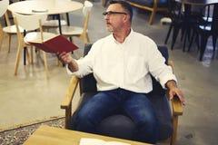 Les gens au travail se reposant dans la chaise confortable à la bibliothèque universitaire moderne pendant la coupure Photo libre de droits