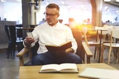 Les gens au wifi coworking de bureau de travail répartissent en zones tandis que des livres de lecture Photographie stock