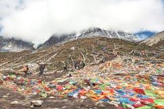 Les gens augmentant et accueillis par des milliers de drapeaux colorés de prière Photographie stock libre de droits