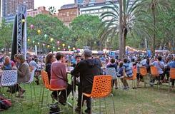 Les gens aux tables apprécient diner et festivités pendant le marché de nouille de nuit Image stock